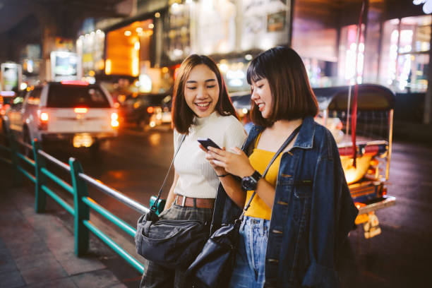 two asian girls in bangkok, looking at their smartphones, chatting about social media - sud est asiatico foto e immagini stock