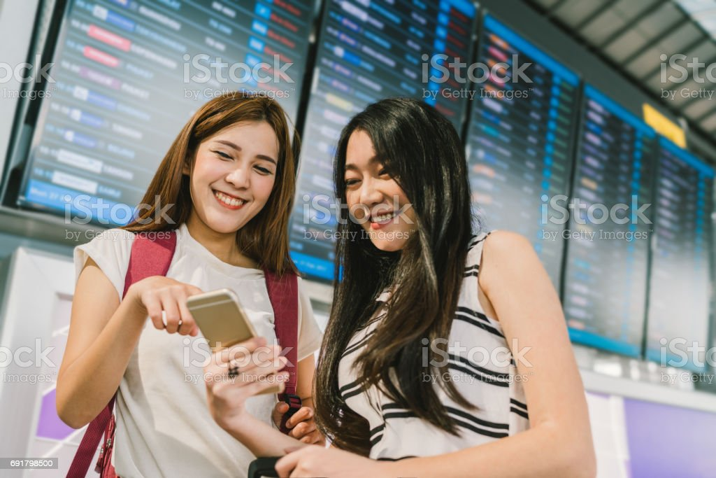 Two Asian girls using smartphone together at flight information board in airport. Online check-in, timetable application, or holiday travel concept stock photo