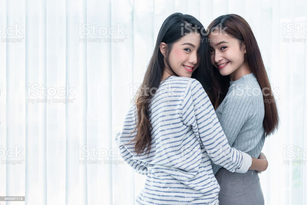 Two Asian Lesbian women looking together in bedroom. Couple people and  Beauty concept. Happy lifestyles and home sweet home theme. Embracing of  homosexual.