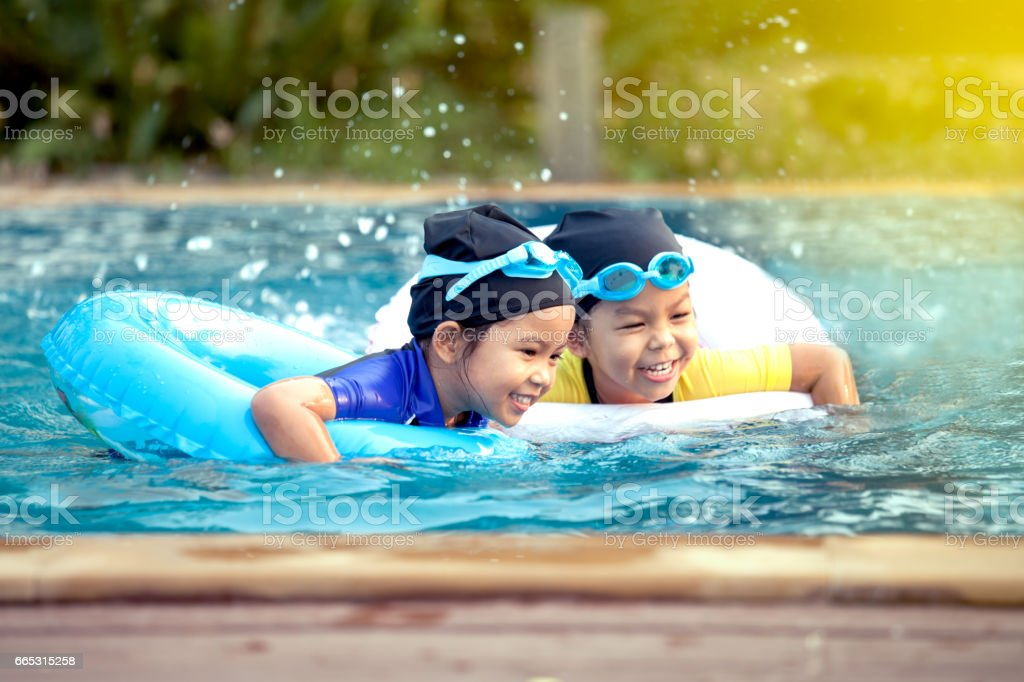 two asian little girls having fun to swim stock photo