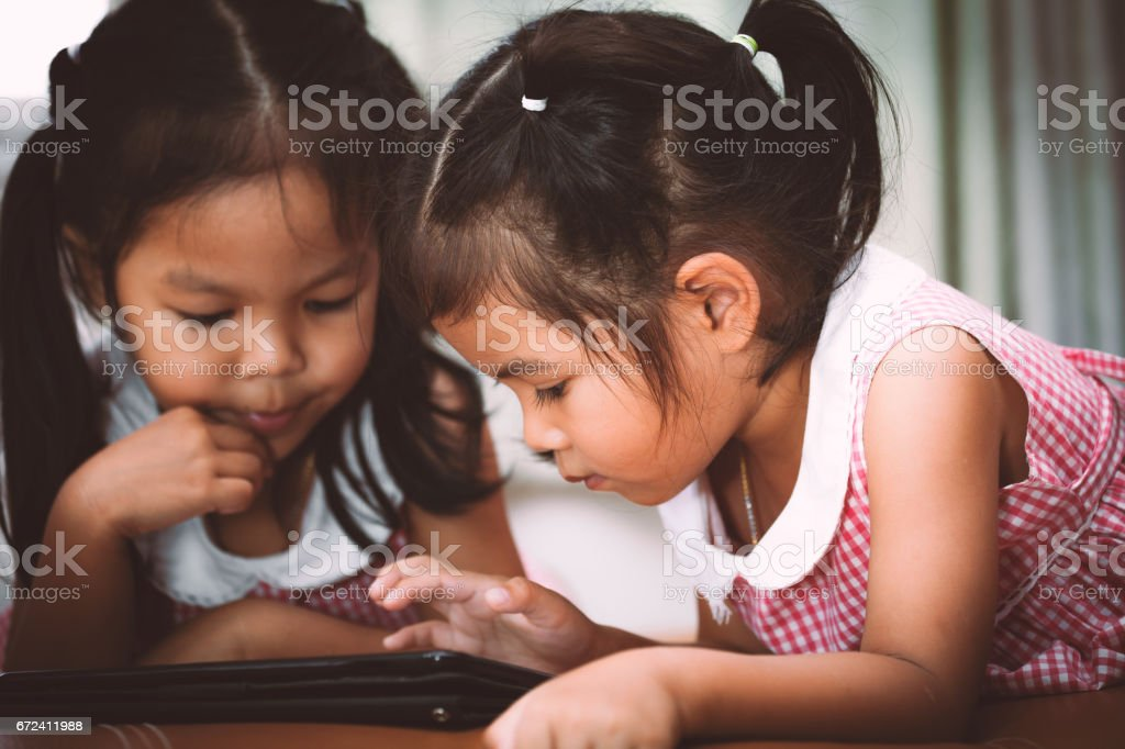 Two asian little girls having fun to watch on tablet stock photo