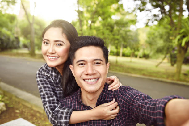 Two asian lovers making a selfie on phone Two asian lovers making a selfie on phone at the park indonesian ethnicity stock pictures, royalty-free photos & images