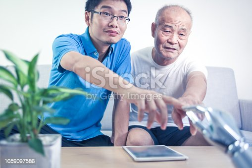 istock Two asian men connecting robot indoors 1059097586