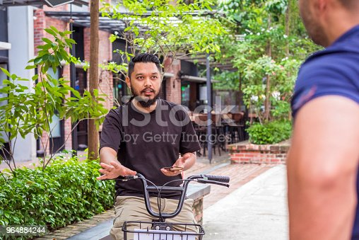 Two Asian Men Talking On The Street Stock Photo & More Pictures of Adult