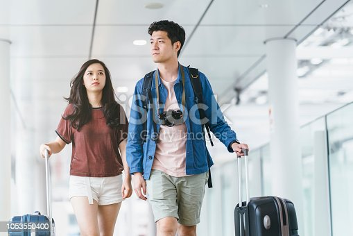 842907838 istock photo Two Asian people walking in airport with thie suitcases 1053550400