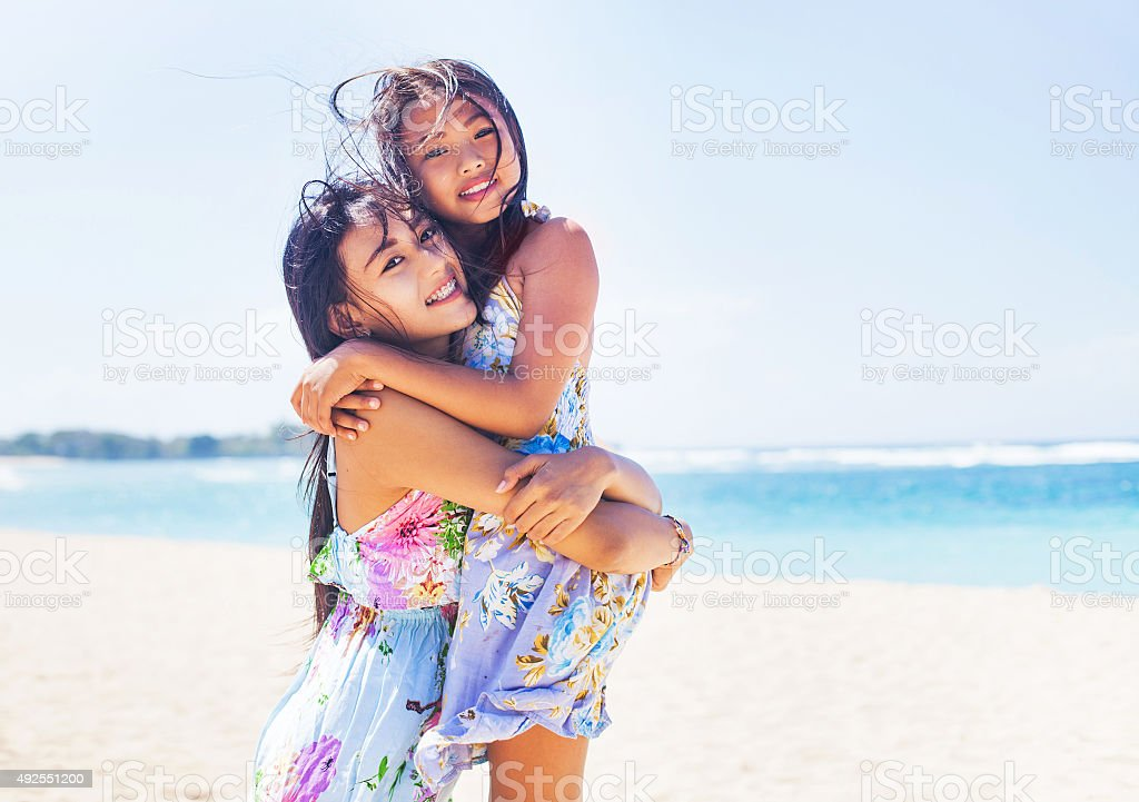 two asian sisters on a beach stock photo