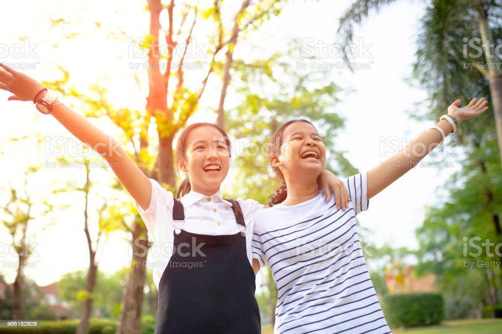 two asian teenager laughing with happiness emotion in green natural park - Royalty-free Adolescente Foto de stock