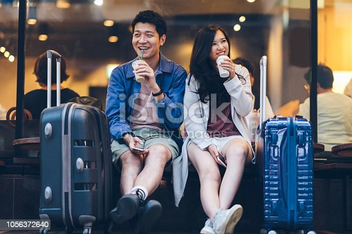 istock Two asian tourists with suitcases spending happy time in cafe 1056372640