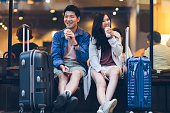 Two Asia tourists are drinking coffee happy in a cafe in their travel destination.