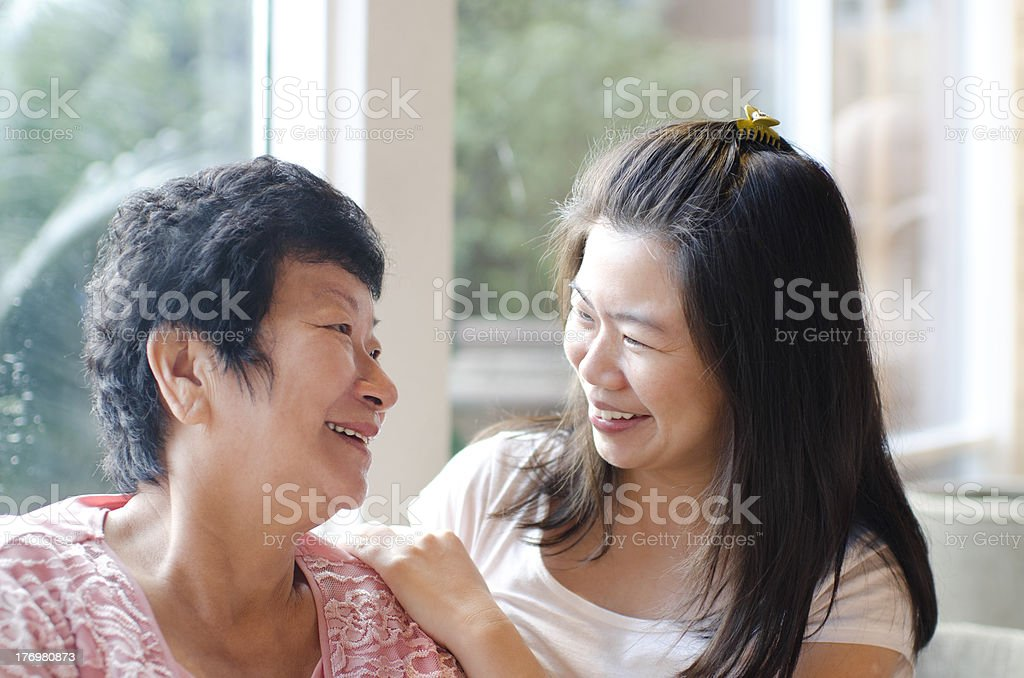 Two Asian women, one elderly, smiling at each other stock photo
