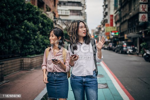 Two women, young women students together in city on the street, using smart phones, looking for apartment.