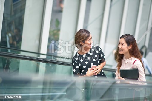 Business colleagues commuting to the city, talking on escalator in glass building
