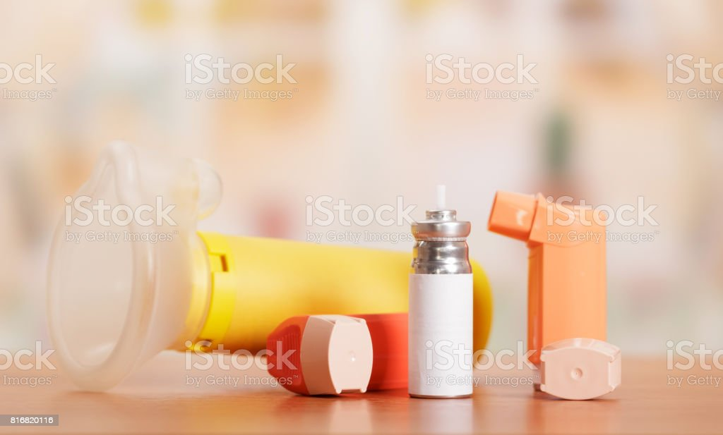 Two asthma inhaler, aerochamber and medication on abstract pink. stock photo