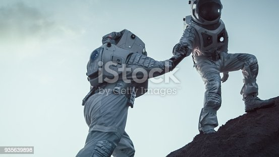 istock Two Astronauts Climbing Mountain Hill Helping Each Other, Reaching the Top. Overcoming Difficulties, Important Moment for the Human Race. 935639898