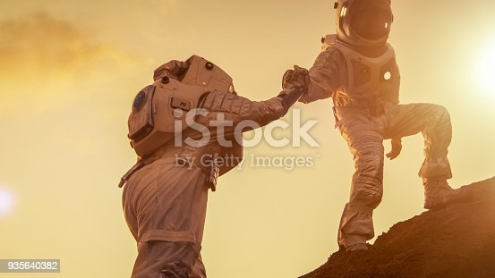 istock Two Astronauts Climbing Mountain Hill Helping Each Other, Reaching the Top. Helping Hand. Overcoming Difficulties, Important Moment for the Human Race. 935640382