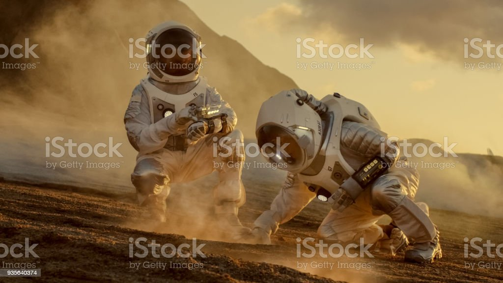 Two Astronauts Collect Soils Samples on Alien Planet, Analyzing Them with Hands Computer. Mars/ Red Planet Manned Expedition. stock photo