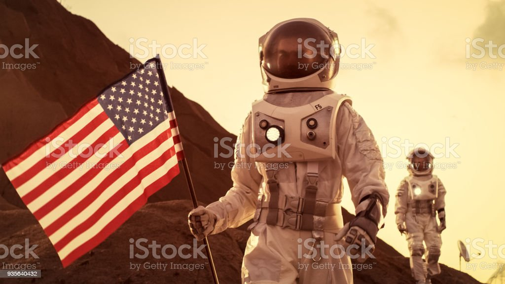 Two Astronauts Explore Mars/ Red Planet. One Cosmonaut Carries American Flag. Technological Advance Brings Space Exploration, Travel, Colonization Concept. stock photo