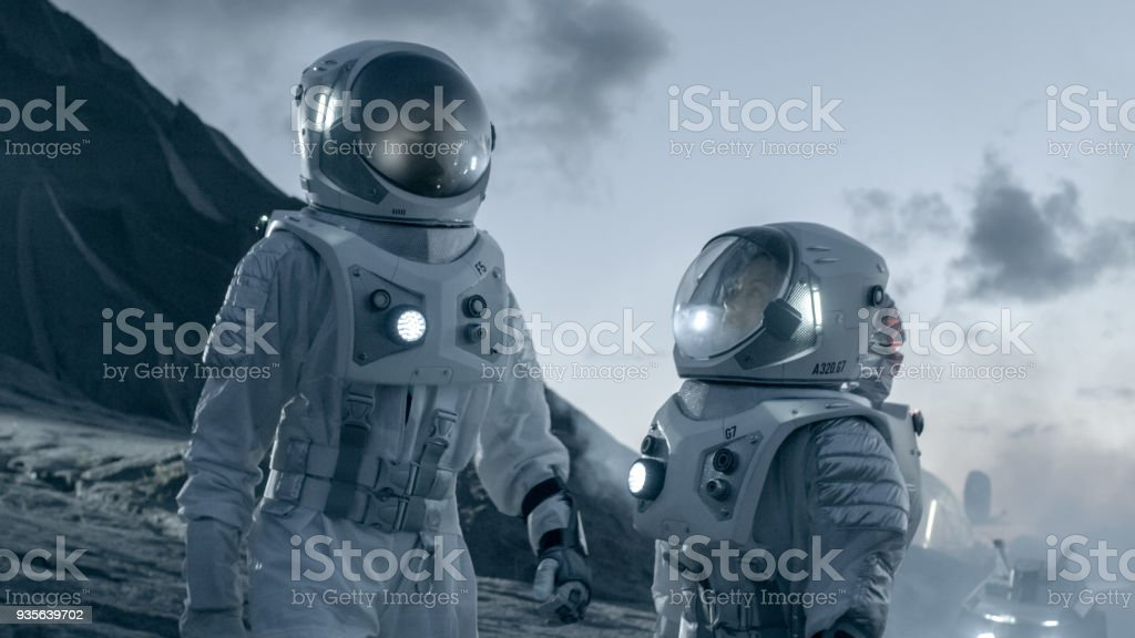 Two Astronauts In Space Suits Confidently Walking On Alien