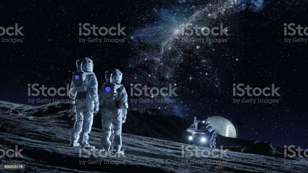 Two Astronauts in Space Suits Stand on the Planet and Looking at the The Milky Way Galaxy. In the Background Lunar Base with Geodesic Dome. Moon Colonization and Space Travel Concept. stock photo