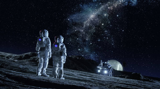 two astronauts in space suits stand on the planet and looking at the the milky way galaxy. in the background lunar base with geodesic dome. moon colonization and space travel concept. - исследование космоса стоковые фото и изображения