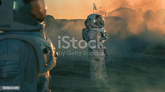 istock Two Astronauts wearing Space Suits Standing on Alien Planet and Looking at Something. Futuristic Space Exploration, Discovery and Colonization. 935640482