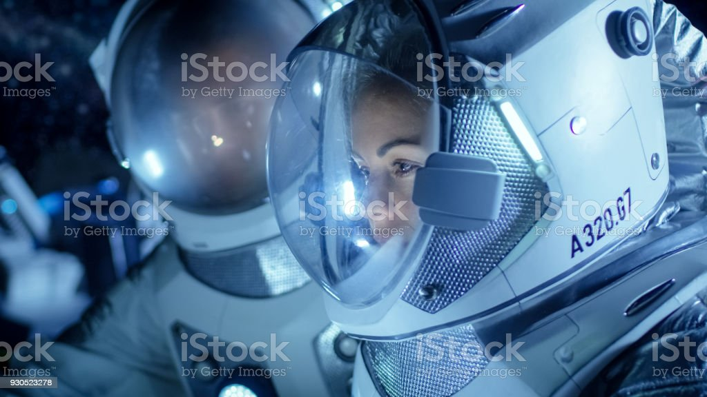 Two Astronauts Wearing Space Suits Talking, Exploring Newly Discovered Planet, Communicating with the Earth. Space Travel, Exploration and Colonization Concept. stock photo