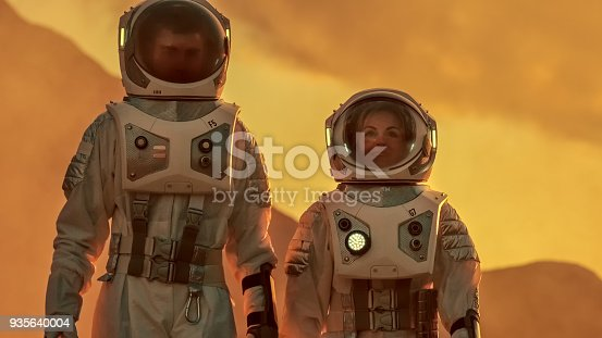 istock Two Astronauts Wearing Space Suits Walk Exploring Mars/ Red Planet. Space Travel, Exploration and Colonization Concept. 935640004