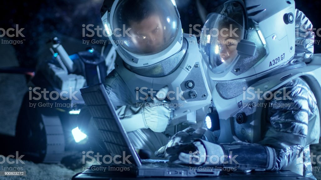 Two Astronauts Wearing Space Suits Work on a Laptop, Exploring Newly Discovered Planet, Communicating with the Earth. Space Travel, Exploration and Colonization Concept. stock photo