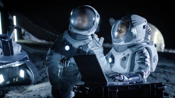 dois astronautas vestindo ternos de espaço de trabalho em um laptop, explorando o recém descoberto planeta, enviar comunicação de sinal para a terra. viagens espaciais, exploração interestelar e conceito de colonização. - exploração espacial - fotografias e filmes do acervo