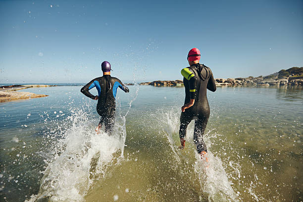 Two athletes competing in a triathlon Two athletic swimmers entering the water with their wetsuits on.  Competitors in wet suits running into the water at the start of a triathlon. wetsuit stock pictures, royalty-free photos & images