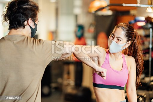 Two athletes in sports clothing are doing elbow bump to great each other in a gym.
