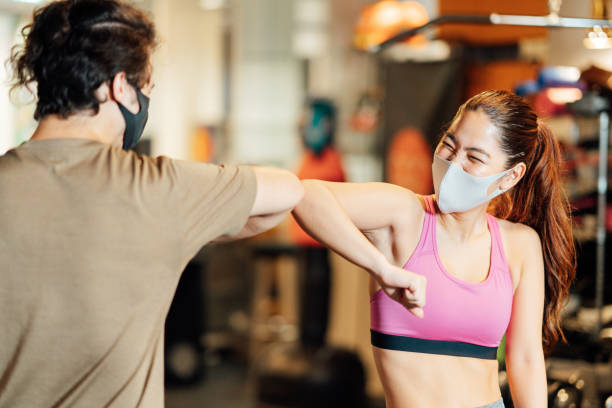 Two athletes doing elbow bump to great each other in gym stock photo
