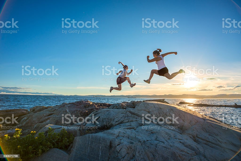 Two Athletic Girls Jumping on Rocky Beach at Sunset stock photo