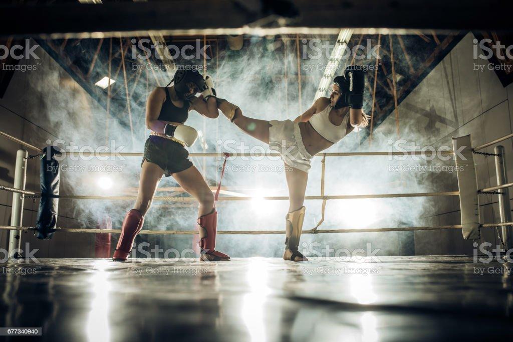 Duas mulheres atléticas, lutando em um jogo de kickboxing em um ginásio. - foto de acervo