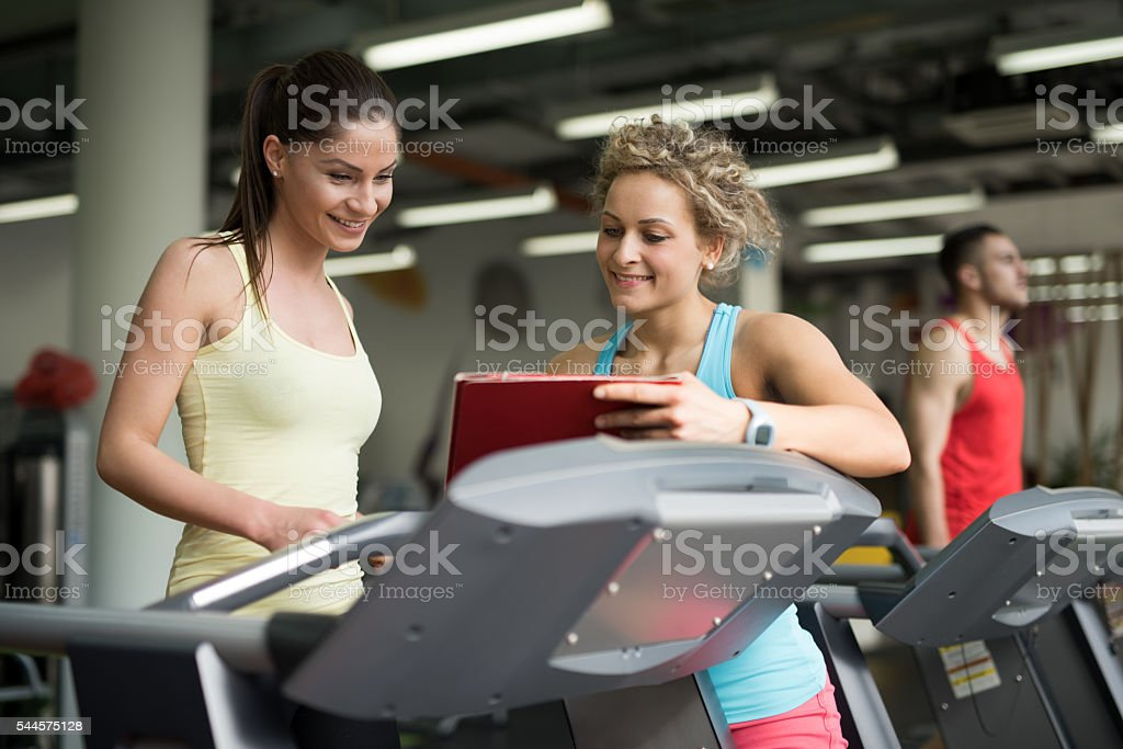 Two athletic women looking at exercise plan in a gym. stock photo