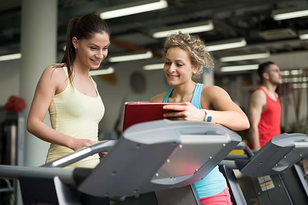 zwei sportliche frau schaut an trainieren sie im fitnessraum. - trainingsplan frauen stock-fotos und bilder