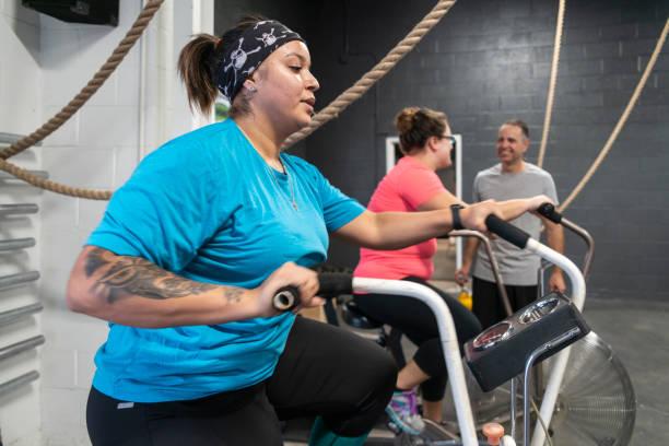 Zwei attraktive Körper-Positive Frauen, Latino und kaukasischen, dabei eine Training auf dem Heimtrainer im Fitness-Studio unter der Aufsicht des Trainers, der Senior kubanischen Hispanic Greis, 55 Jahre – Foto