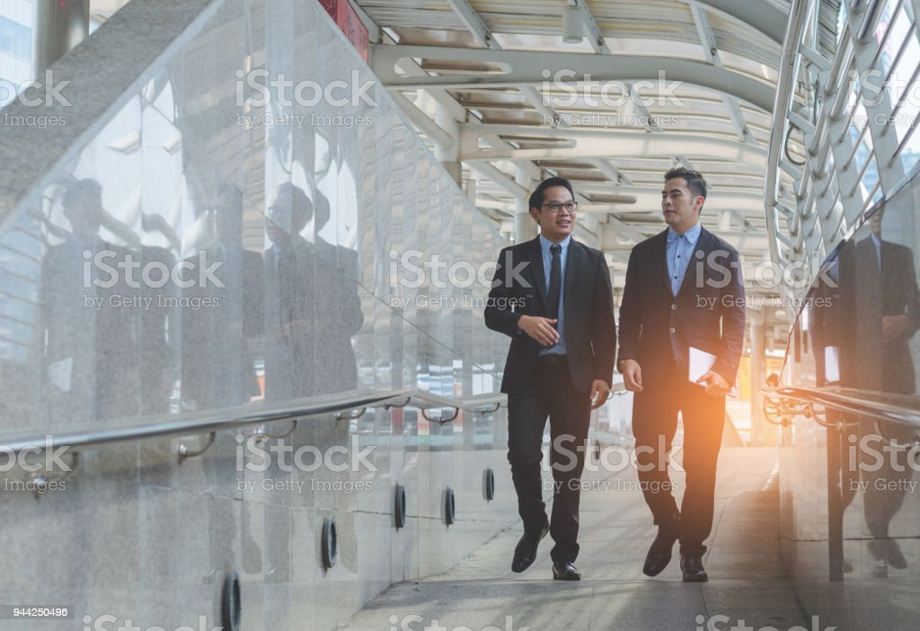 two attractive business man discussion and walking at outdoor on morning. stock photo