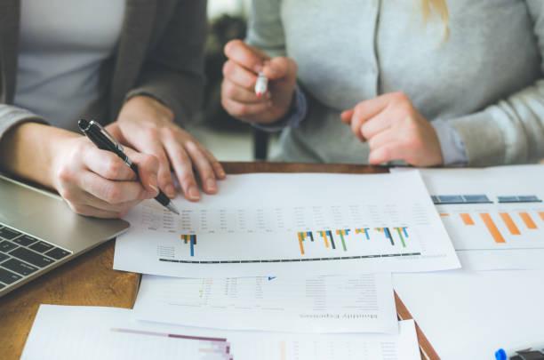 två attraktiva kvinna lagarbete arbetar på tabell med strategi och analysera från beslutsdokument i planerar nya projekt. - projektledning bildbanksfoton och bilder