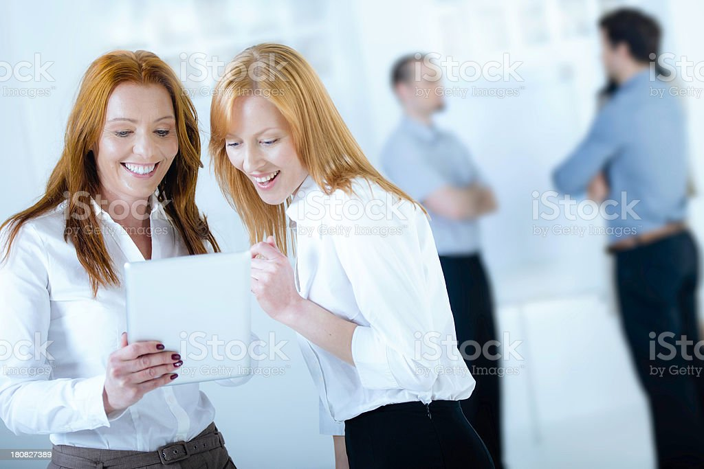 Two attractive businesswomen with digital tablet surfing the net royalty-free stock photo