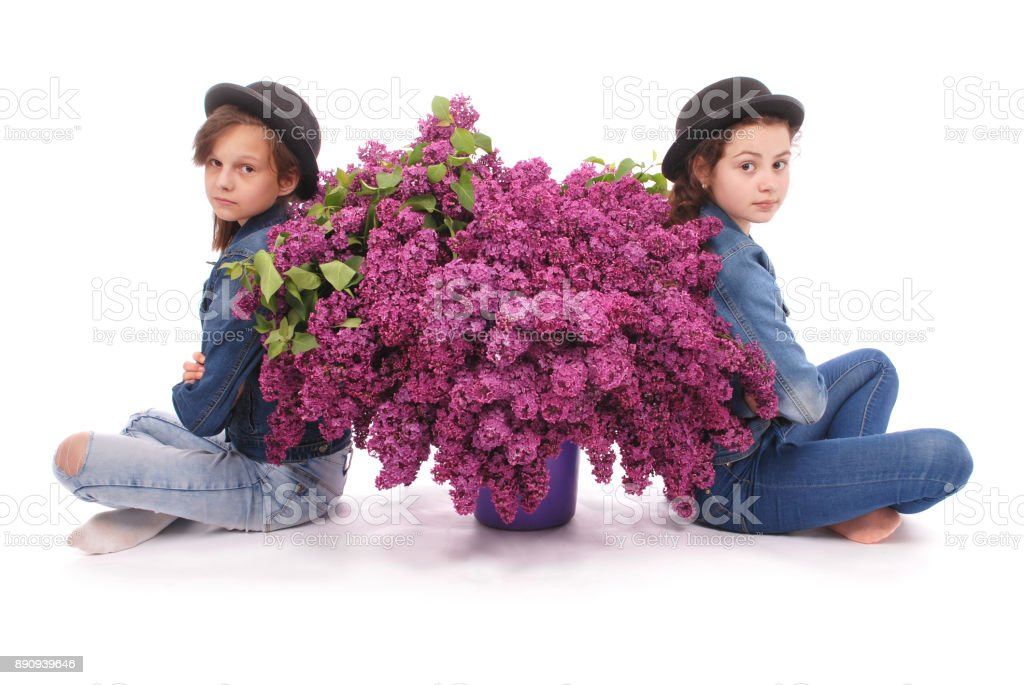 Two attractive girl sits with lilac. stock photo
