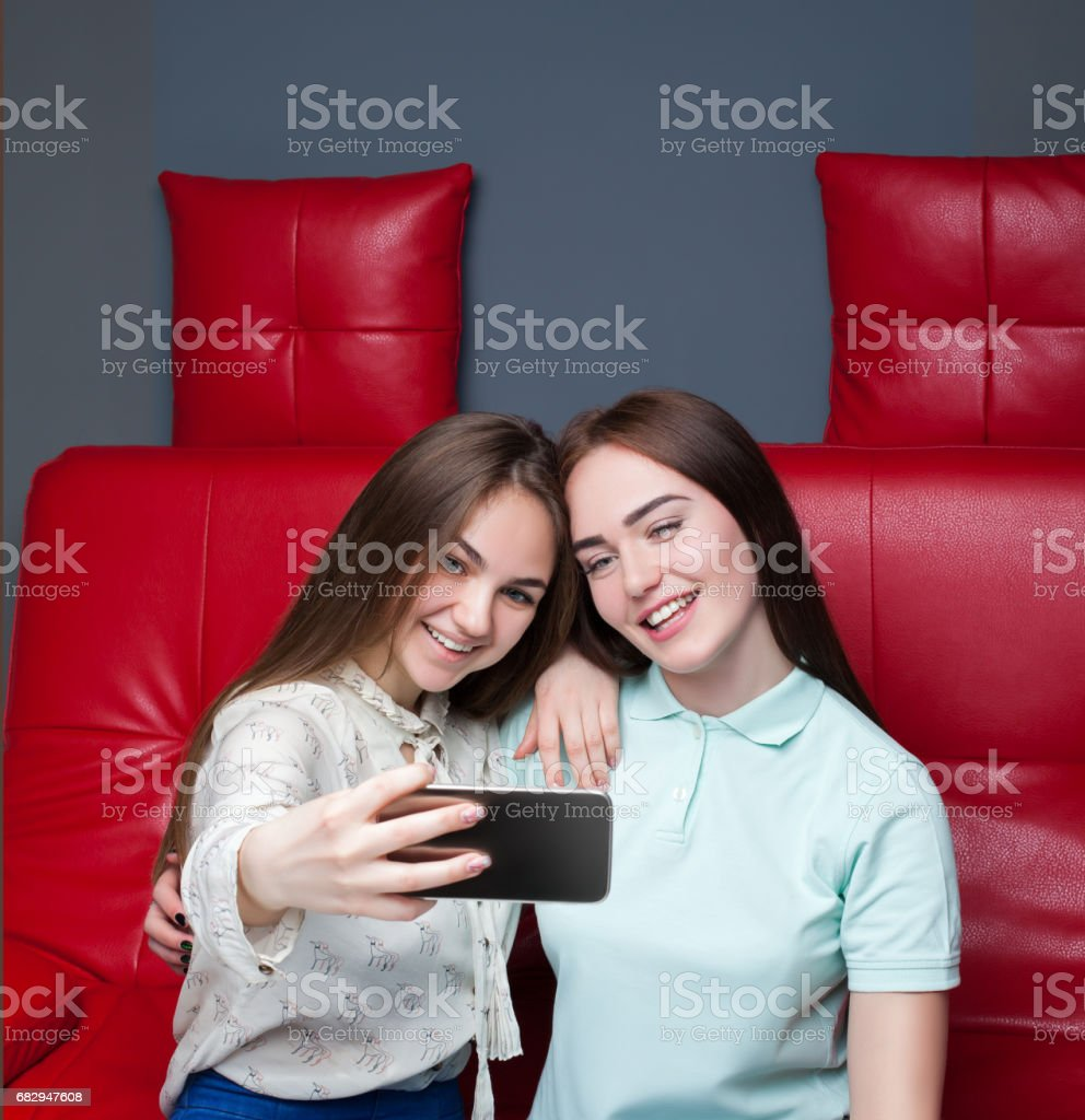Two attractive girlfriends makes selfie on camera royalty-free stock photo