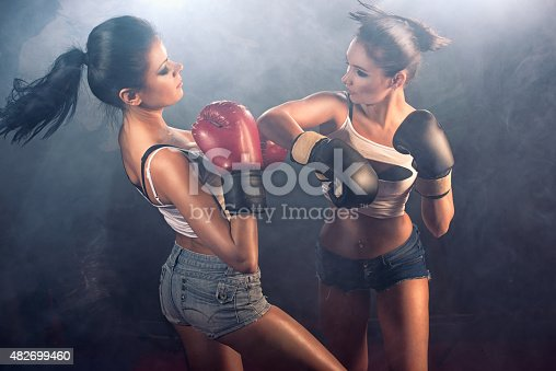Two attractive athletic girls sparring at gym