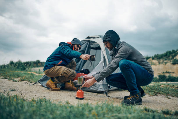 Two attractive men crouching by the tent in the nature and cooking morning coffee. stock photo