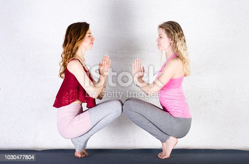 916126642istockphoto Two attractive sports girls practice yoga in a fitness class. Group of young women stretching 1030477804