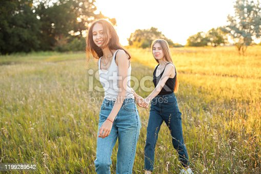 1092709104 istock photo Two attractive young women are walking outdoors 1199289542