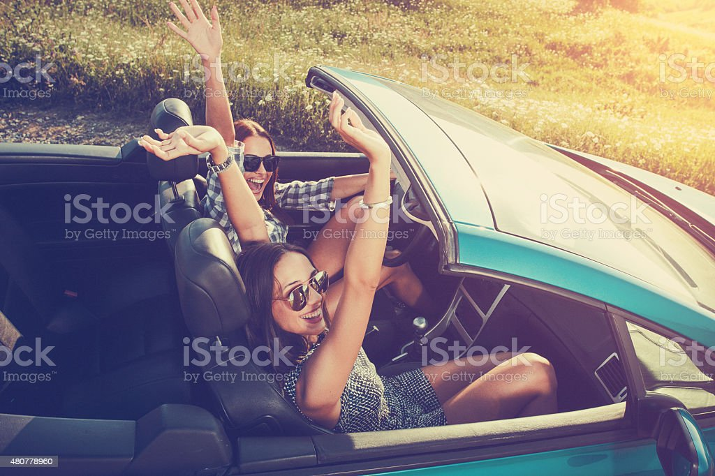 Two attractive young women in a convertible stock photo