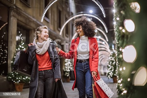 Pretty Young Female Friends Smiling Broadly In Cheerful Manner Having Fun At Shopping Mall, Buying Christmas Gifts