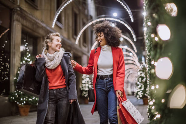 Two Attractive Young Women In Christmas Shopping Pretty Young Female Friends Smiling Broadly In Cheerful Manner Having Fun At Shopping Mall, Buying Christmas Gifts buying stock pictures, royalty-free photos & images