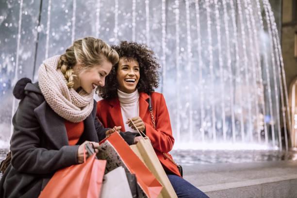 dos mujeres jóvenes atractivas en compras navideñas - moda de invierno fotografías e imágenes de stock
